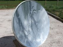 Parabolic mirror solar oven starting fire on stick. From rays stock photography