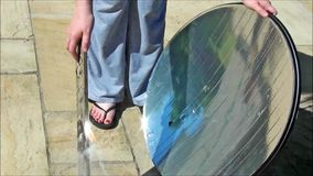 Parabolic mirror solar oven starting fire on stick. From rays royalty free stock photography