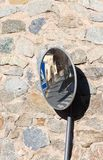 Parabolic road mirror. Parabolic round road mirror with town reflection on a house wall stock images