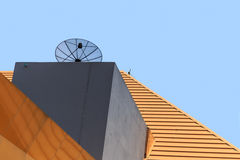 Parabolic satellite dish on the modern building roof. Royalty Free Stock Photo