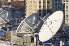 Parabolic satellite dish space technology receivers over the cit Stock Photos