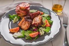 Paraboloïdes chauds de viande Les nervures de porc ont grillé avec de la salade et des pommes d'un plat Images stock