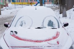 Parabrezza congelato dell'automobile coperto di ghiaccio e di neve un giorno di inverno Sorriso fotografie stock libere da diritti
