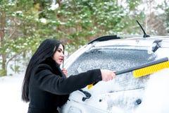 Parabrezza dell'automobile di pulizia della donna ruspa spianatrice felice di inverno della neve di giovane Immagini Stock