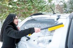 Parabrezza dell'automobile di pulizia della donna ruspa spianatrice felice di inverno della neve di giovane Fotografie Stock Libere da Diritti