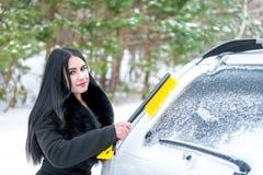 Parabrezza dell'automobile di pulizia della donna ruspa spianatrice felice di inverno della neve di giovane Immagine Stock Libera da Diritti