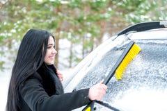 Parabrezza dell'automobile di pulizia della donna ruspa spianatrice felice di inverno della neve di giovane Fotografia Stock