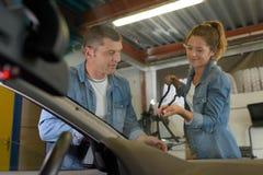 Parabrisas cambiante del mecánico de sexo femenino en el coche imagenes de archivo