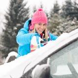 Parabrisas del coche de la limpieza de la mujer del invierno de la nieve Fotografía de archivo