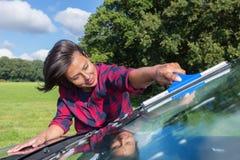 Parabrisas del coche de la limpieza de la mujer joven en naturaleza Imagenes de archivo