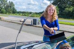 Parabrisas del coche de la mujer que se lava holandesa joven Imagen de archivo libre de regalías