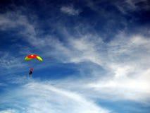 Paracaídas colorido contra el cielo azul y las nubes blancas Fotografía de archivo