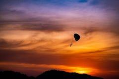 Paracaídas en la puesta del sol de la playa foto de archivo