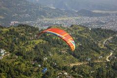 Paracaídas rojo con una raya azul de un vuelo del ala flexible en tándem contra un fondo de montañas verdes y una ciudad en el va fotos de archivo