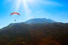 Paracaídas rojo en el cielo sobre las montañas Fotos de archivo libres de regalías