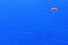 Paracaídas rojo en el cielo sobre el mar azul Imagen del minimalismo concepto del recorrido Fotografía de archivo libre de regalías