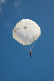 Paracadute rotondo bianco sul cielo blu del fondo Immagine Stock