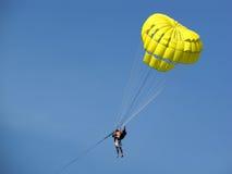 Paracadute umani di colore giallo della holding fotografie stock libere da diritti