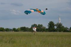 Paracaidista con el paracaídas azul contra el cielo azul claro Imágenes de archivo libres de regalías