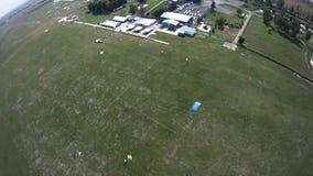 Paracaidista que vuela sobre campo verde Momento de aterrizaje Deporte activo extremo almacen de metraje de vídeo