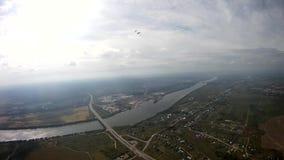 Paracaidista que vuela sobre el campo verde, río Deporte activo extremo adrenalina almacen de video