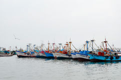 PARACAS, PERU- 11 JUNE, 2013: Old local fishing boat with fishing nets and seagulls anchored in the harbour Stock Photo