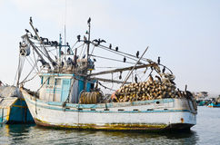 PARACAS, PERU- 11 JUNE, 2013: Old local fishing boat with fishing nets and seagulls anchored in the harbour Stock Photos