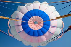 Parachute. Bright colourful parachute in the blue sky Stock Image