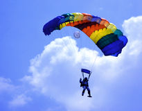 Parachute. Colorful parachute against blue sky and white feathery clouds Stock Photography