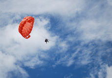 Parachute. Two persons parasailing through the air with a red parachute Royalty Free Stock Images