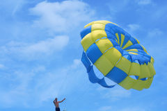 Parachute against the sky. Young man holding the parachute against the sky Royalty Free Stock Photos