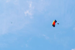 Parachute and airplane with blue sky on the background. Skydiver on parachute and airplane are sliding with blue sky on the background royalty free stock images
