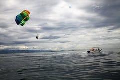 Parachute ascensionnel de touristes au-dessus de l'océan photo stock