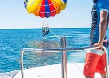 Parachute ascensionnel heureux de couples en plage Dominicana en été Couples sous le plein vol accrochant de parachute Image libre de droits