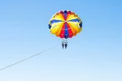 Parachute ascensionnel heureux de couples en plage Dominicana en été Couples sous le plein vol accrochant de parachute Avoir l'am Photo libre de droits