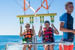 Parachute ascensionnel heureux de couples en plage Dominicana en été Couples sous le plein vol accrochant de parachute Avoir l'am Image stock