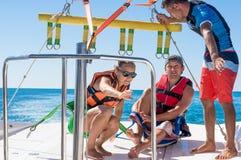 Parachute ascensionnel heureux de couples en plage Dominicana en été Couples sous le plein vol accrochant de parachute Avoir l'am Photo stock
