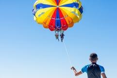 Parachute ascensionnel heureux de couples en plage Dominicana en été Couples sous le plein vol accrochant de parachute Avoir l'am Image libre de droits