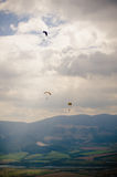 Parachute and clouds. Three parachutes in the air, mountains and clouds in background Stock Image