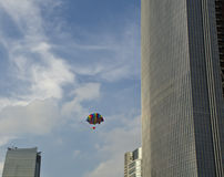 Parachute among the high building. A toy parachute drops from the sky Royalty Free Stock Photography