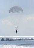 Parachute jump. A man with a parachute is flying against the sky Stock Photos