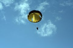 Parachute jumper. Looking up into the sunlit round parachute of a paratrooper, with a bright blue sunny sky royalty free stock photo