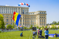 Parachutist in the air. Parachutist landing with Romanian flag next to Palace of Parliament at the Red Bull Ordinul Smaranda competition on June 7, 2014 in Royalty Free Stock Image