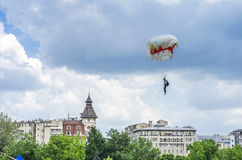 Parachute jumper lands in city Stock Images