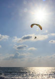Parachute jumper on motorized parachute flying over the sea Stock Photos