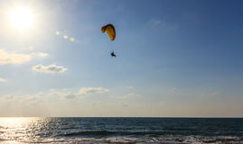 Parachute jumper on motorized parachute flying over the sea Stock Image