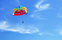 Parachute jumping. Colorful parachute is in the sky, under the clouds. Stock Photos
