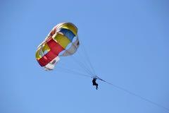 Parachute lumineux contre le ciel bleu Photos libres de droits