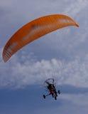 Parachute motor glider. Orange colored parachute motor glider or paraglider in action Stock Photography