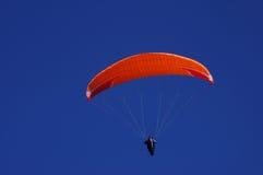 Parachute orange lumineux un beau jour ensoleillé Images libres de droits
